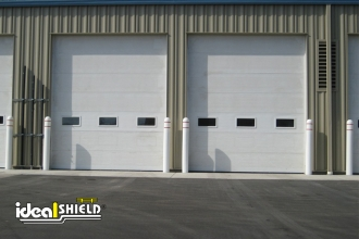 "1/8"" White Bollard Covers Protecting Garage Doors"