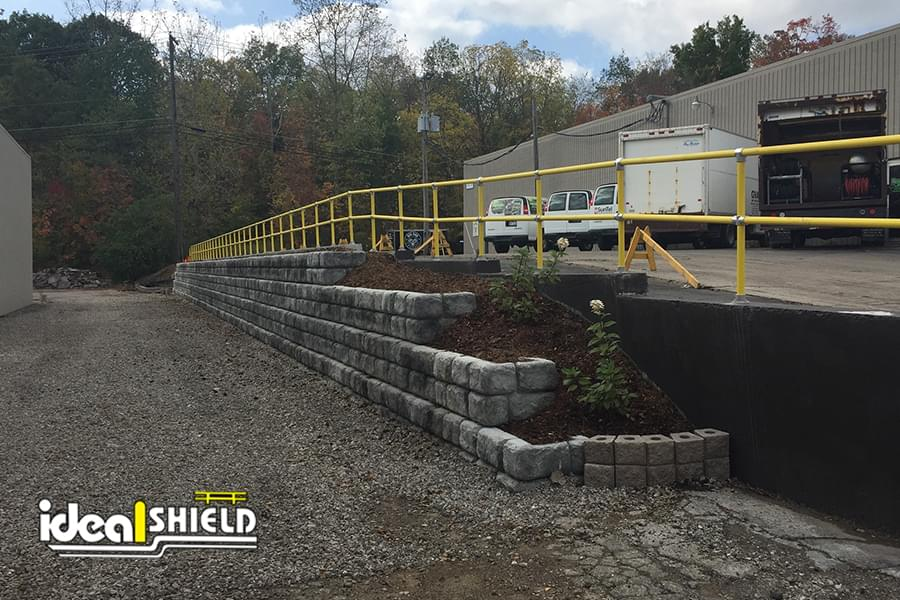 Ideal Shield's yellow Steel Pipe and Plastic handrail lining a truck parking lot ledge
