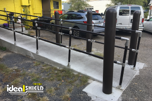 Ideal Shield's Steel Pipe and Plastic Handrail with Bollard Covers lining a handicap accessible ramp at a restaurant entrance