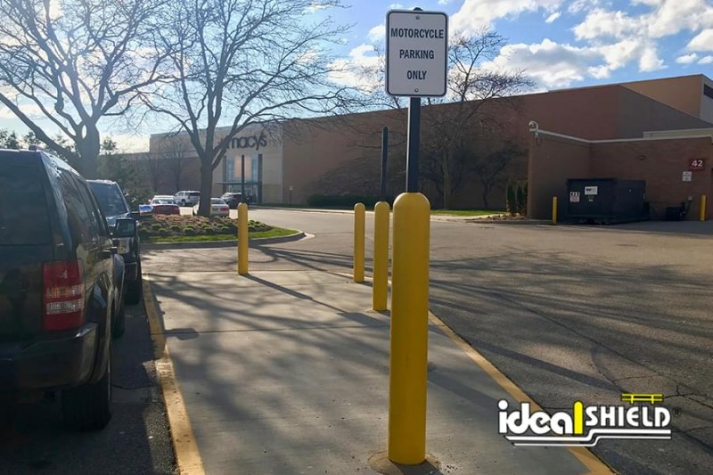 Ideal Shield's six inch Yellow Bollard Sign Systems used for Motorcycle Parking Only Signs in Mall Parking Lot