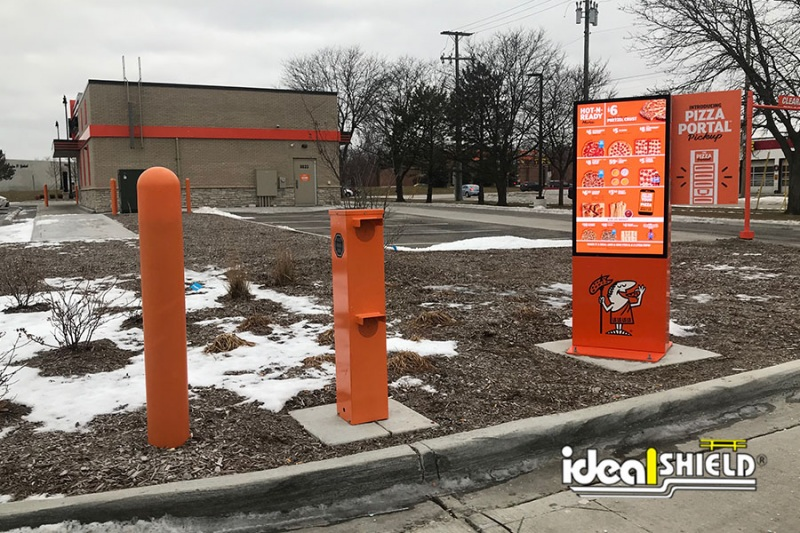 Ideal Shield's orange bollard covers protecting a Little Caesars' drive-thru speaker box
