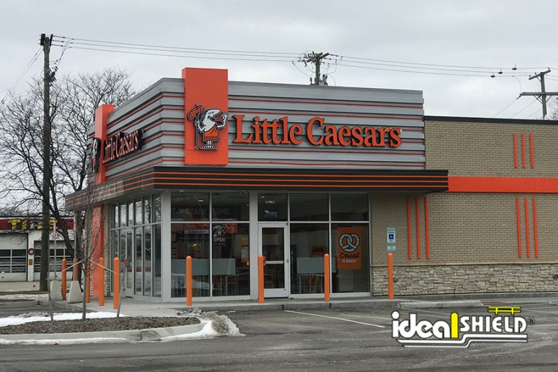 Ideal Shield's orange bollard covers protecting a Little Caesars storefront