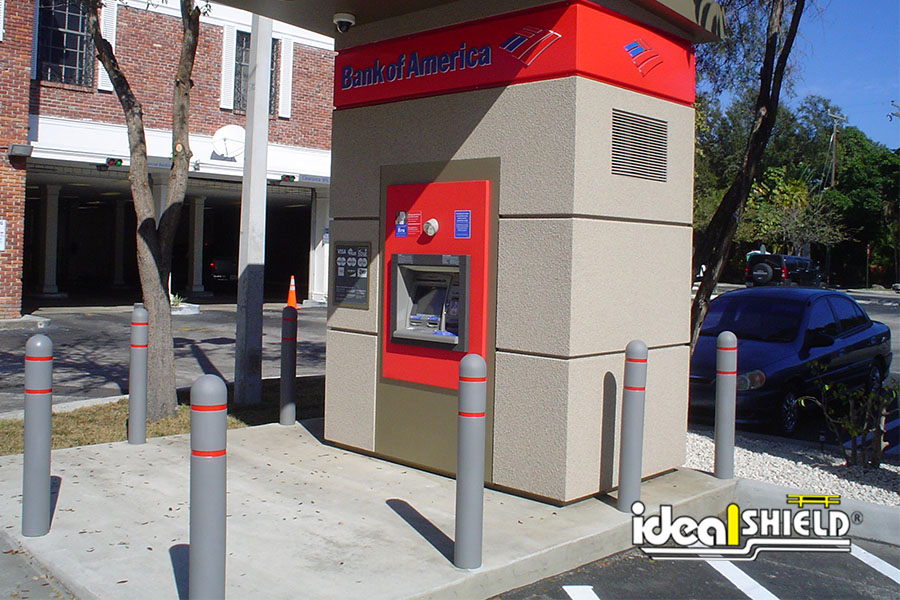 Ideal Shield's Gray Reflective Bollard Covers with Red Tape at a Bank of America ATM