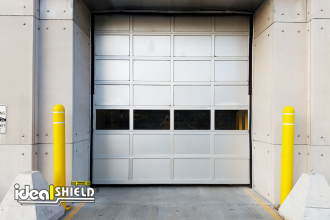 Ideal Shield's yellow Bollard Covers with grooves and white reflective tape guarding overhead doors