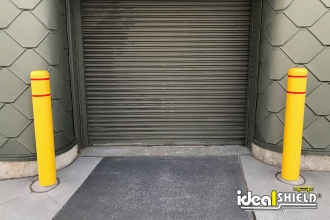 """Ideal Shield's 6"""" flat top bollard covers with reflective white tape guarding an overhead door"""
