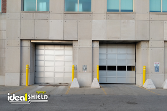 humana 2Ideal Shield's yellow Bollard Covers with grooves and white reflective tape guarding overhead doors