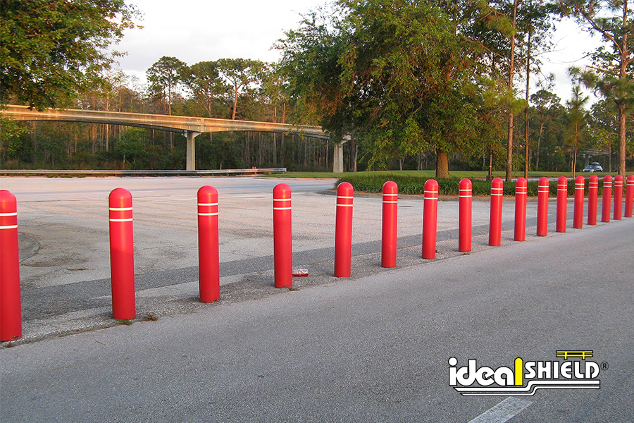 "Ideal Shield's red 1/4"" Bollard Covers with White Reflective Tape used as a Parking Lot Separator"