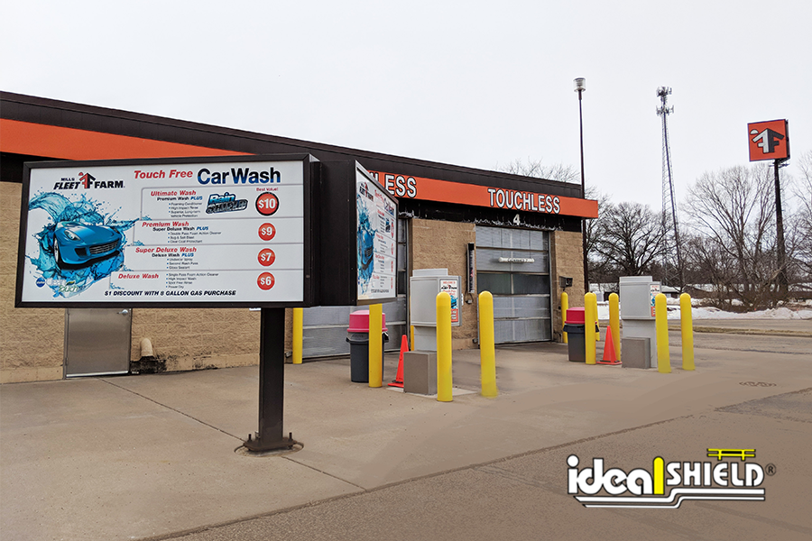 "Ideal Shield's yellow 1/4"" Bollard Covers used to guard a Car Wash"