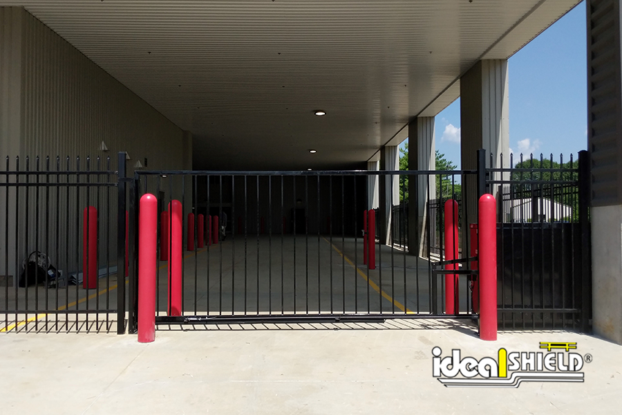 Ideal Shield's red bollard covers used to protect a gate entrance