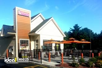 "Ideal Shield's 1/8"" plastic bollard covers used to guard outdoor patio of a Dunkin' Donuts"