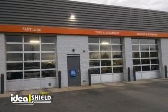 "Ideal Shield's dark grey plastic 1/8"" Bollard Covers with orange reflective tape guarding garage doors at Quick Lane"