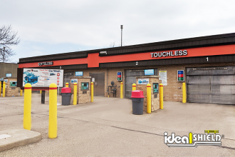 "Ideal Shield's yellow plastic 1/8"" bollard covers used to guard payment kiosks at a car wash"
