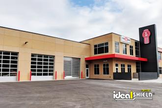 "Ideal Shield's red plastic 1/8"" bollard covers guarding garage doors"