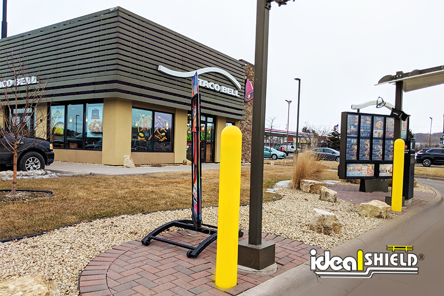 """Ideal Shield's yellow plastic 1/8"""" bollard covers protecting a drive-thru at Taco Bell"""