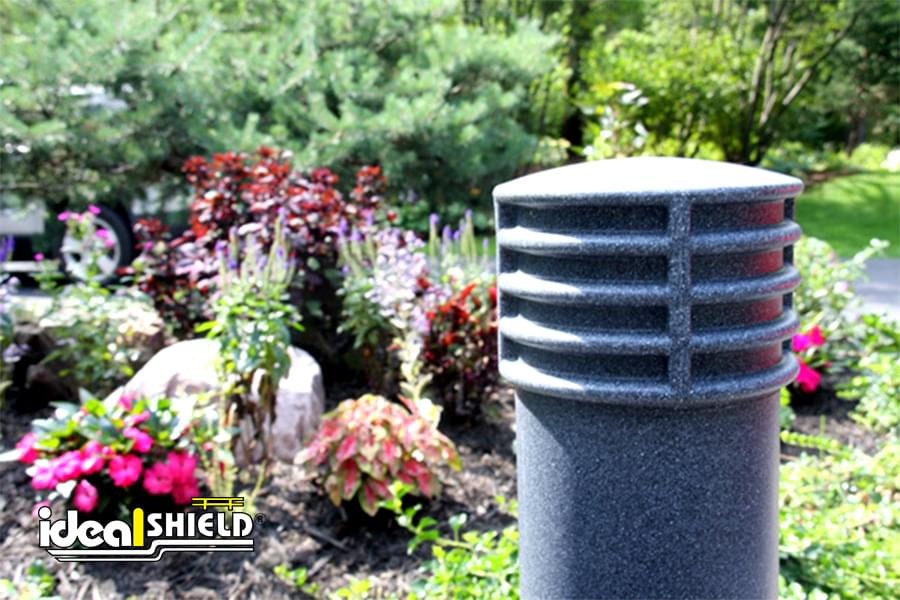 "Ideal Shield's 6"" Cinco Decorative Bollard Cover in a garden setting"