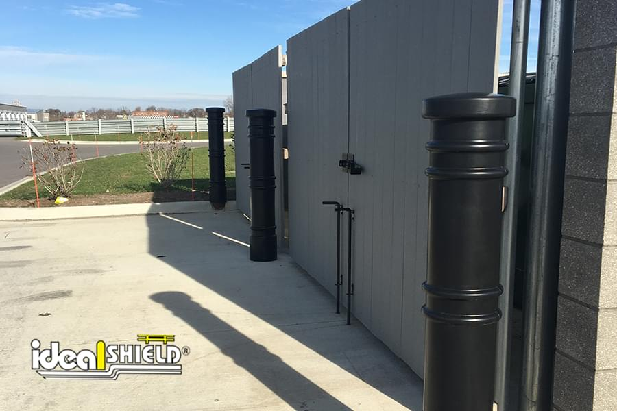 "Ideal Shield's black plastic 6"" Metro Decorative Bollard Covers guarding a parking lot dumpster area"