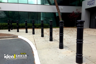 "Ideal Shield's 6"" Metro Decorative Bollard Covers used to line a pedestrian sidewalk and building entrance"