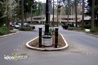 "Ideal Shield's black plastic 6"" Metro Decorative Bollard Covers used at a parking lot"