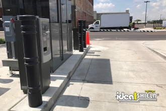 "Ideal Shield's black plastic 6"" Metro Decorative Bollard Covers guarding a parking lot lift gate"