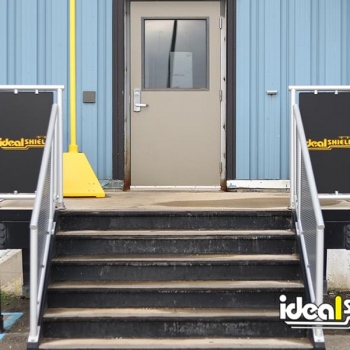 Custom cut handrail infill panels with Ideal Shield's logo