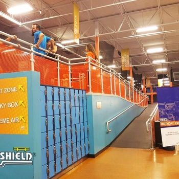 Ideal Shield's Aluminum Handrail with orange infill panels for SkyZone