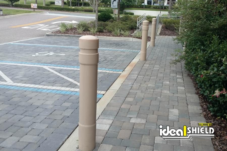 Ideal Shield's Tan 6 Inch Architectural Bollard Covers at a Liquor Store Parking Lot