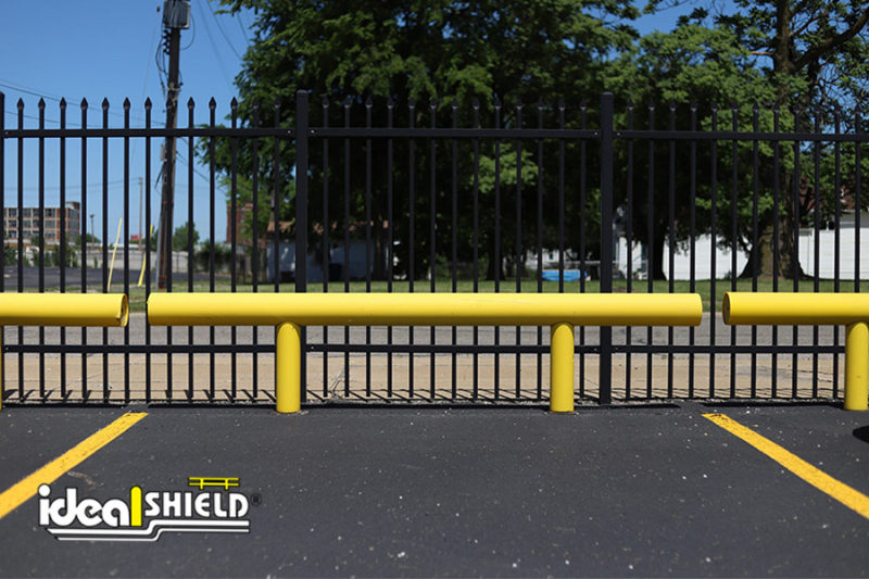 Ideal Shield's One Line Guardrail protecting a parking lot fence
