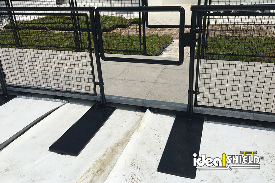 Ideal Shield's black powder-coated Aluminum Handrail with gate and non-penetrating  Roof Fall Protection Base Plates  hidden by garden boxes