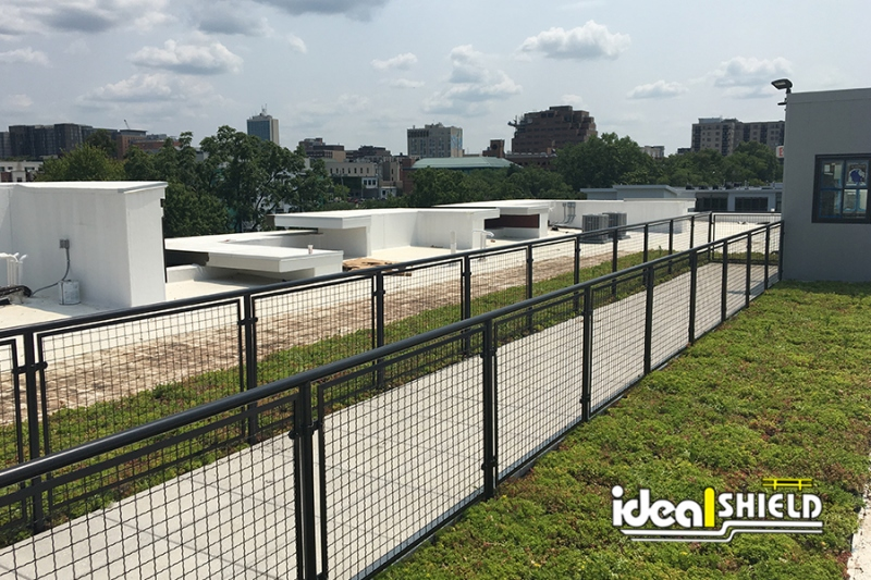 Ideal Shield's black powder-coated Aluminum Handrail with non-penetrating  Roof Fall Protection Base Plates  hidden by garden boxes