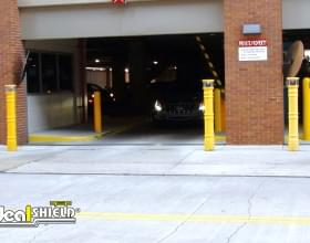 Ideal Shield's UV Lighted Bollard Covers at a Parking Garage Entrance
