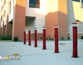 Ideal Shield's Red UV Lighted Bollard Covers lighting a Parking Lot