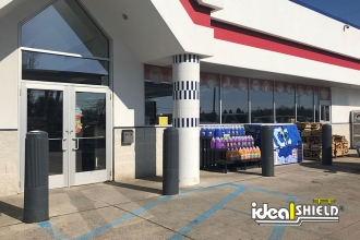 "Ideal Shield's 10"" Ribbed Decorative Bollard Covers used for storefront protection outside of a gas station"