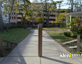 "Ideal Shield's 6"" Bronze Skyline Decorative Bollard Cover used for campus sidewalk protection"