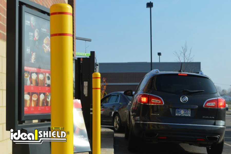 Ideal Shield's Yellow Flat Top Bollard Covers with Red Reflective Tape used for fast food drive thru protection