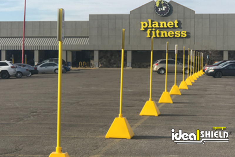 Ideal Shield's Yellow Pyramid Sign Bases lining the Planet Fitness parking lot