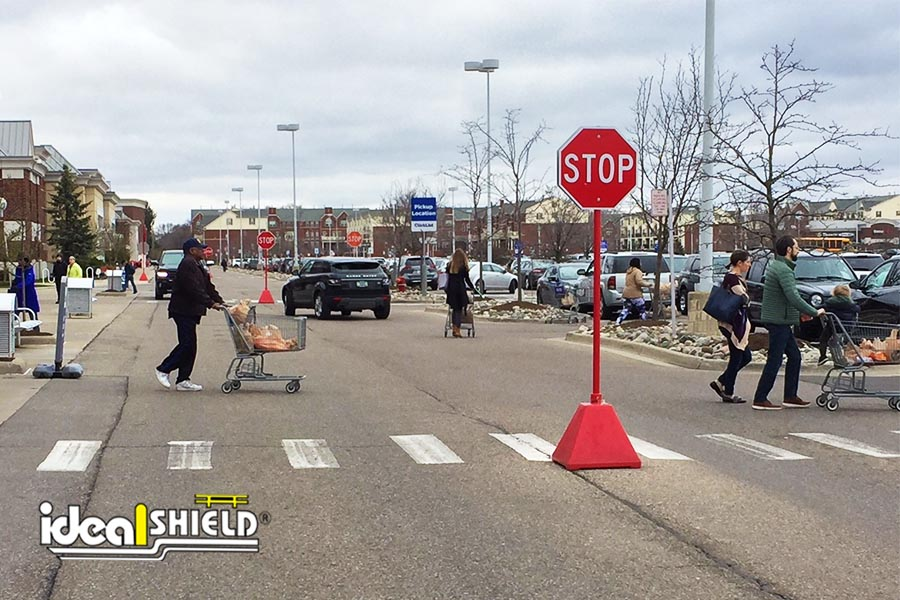 Ideal Shield's Pyramid Sign Base Used as a Stop Sign in a Grocery Store Parking Lot