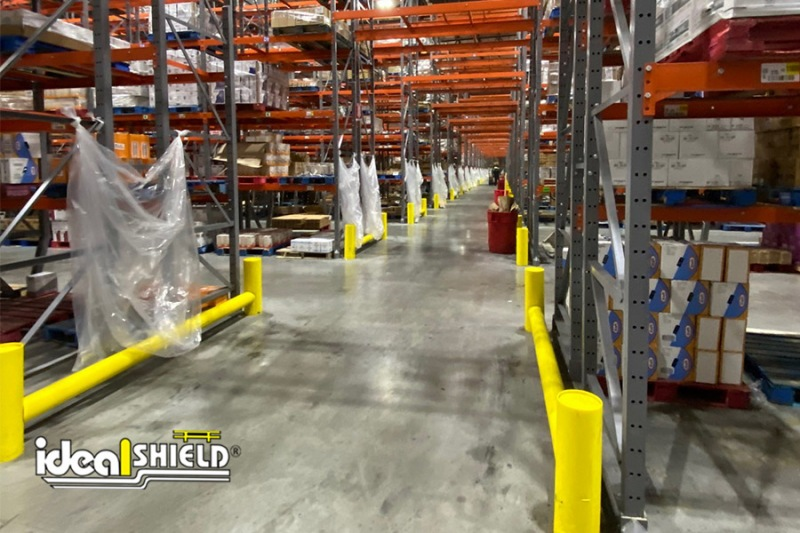 Ideal Shield's One-Line Core-in Extended Rack Guard lining a pallet rack aisle way to ensure protection from forklifts