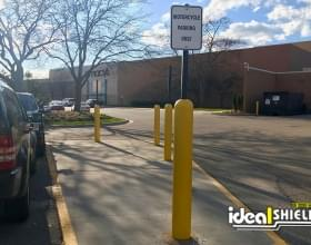 Ideal Shield's yellow Bollard Sign Systems used for Motorcycle Parking Only signs in a mall parking lot