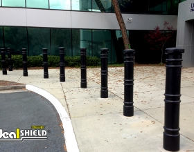 "Ideal Shield's 6"" Black Cinco Decorative Bollard Covers at a storefront"