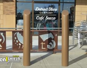 "Ideal Shield's 6"" Bronze Decorative Skyline Bollard Covers guarding a storefront"