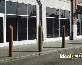 "Ideal Shield's 6"" Bronze Decorative Skyline Bollard Covers guarding a sidewalk"
