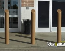 "Ideal Shield's 6"" Metallic Bronze Decorative Skyline Bollard Covers guarding a storefront"
