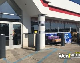 "Ideal Shield's 10"" Ribbed Decorative Bollard Covers used for storefront protection at a gas station"