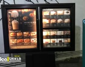 "Ideal Shield's 6"" Skyline Bollard Covers with custom decal at a Starbucks drive-thru"