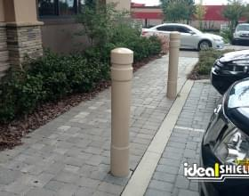 "Ideal Shield's 6"" Tan Architectural Decorative Bollard Covers at a Liquor Store"