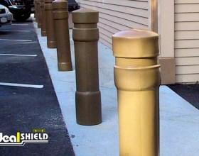 "Ideal Shield's 6"" Black Skyline Bollard Covers protecting a storefront sidewalk"