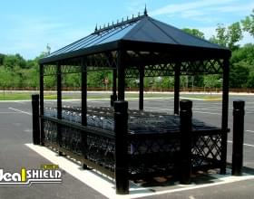 "Ideal Shield's 6"" Black Architectural Bollard Covers protecting a cart corral"