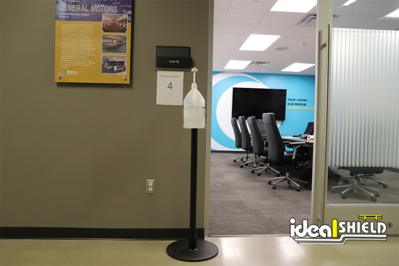 Ideal Shield's Sanitizer Stand in all black with Cup Mount outside of a conference room