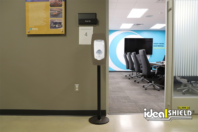 Ideal Shield's Sanitizer Stand in all black with Touchless Dispenser Mount outside of a conference room