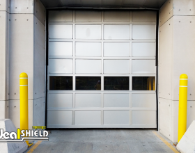 Ideal Shield's yellow Bollard Covers with grooves and white reflective tape guarding an overhead door